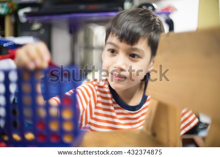 Little boy playing connect four game soft focus at eye contact - stock photo