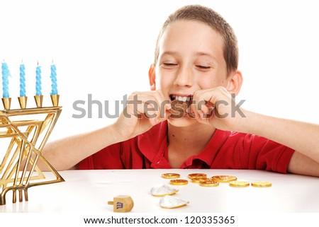 Little boy playing dreidel and eating chocolate Hanukkah gelt.  White background. - stock photo