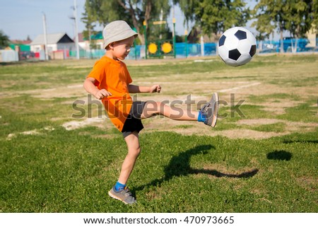 little boy playing football. Child in orange t-shirt hits the ball