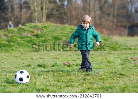 Little boy playing football or soccer on cold spring or autumn day