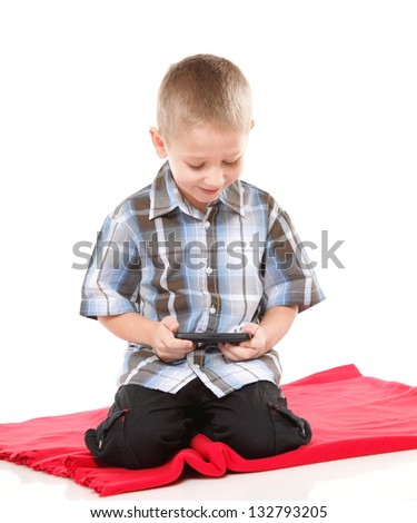 Little boy playing games on smartphone or reading a text message isolated on white background