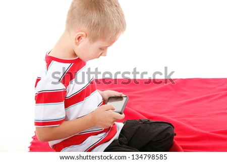 Little boy playing games on smartphone or reading a text message isolated on white background - stock photo