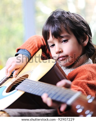 Little boy playing guitar at home - stock photo