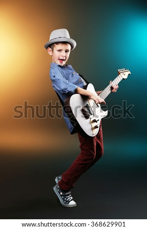 Little boy playing guitar on a dark lighted background - stock photo