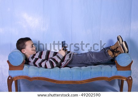 Little Boy Playing Hand held Video Game on the Couch