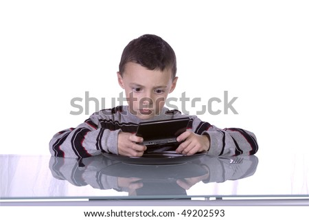 Little Boy Playing Hand held Video Game while Waiting for Dinner at the Table