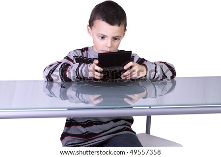 Little Boy Playing Handheld Video Game while Waiting for Dinner at the Table