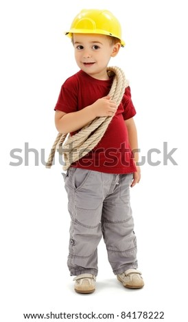 Little boy playing handyman, holding rope and wearing yellow protective helmet, imitating builder - stock photo