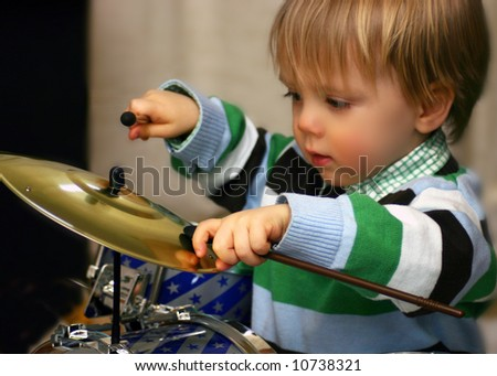 Little boy playing his toy drums - stock photo