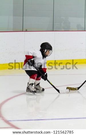 Little boy playing ice hockey - stock photo