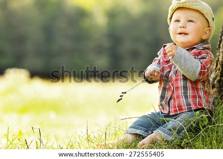 little boy playing in a cowboy hat on the nature