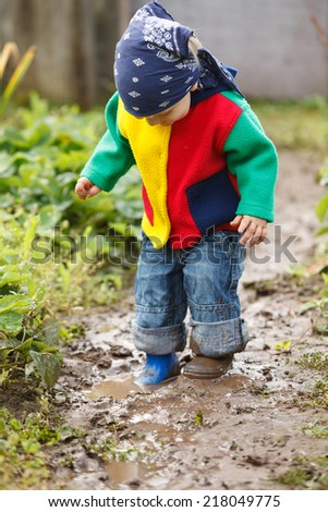 Little boy playing in mud - stock photo