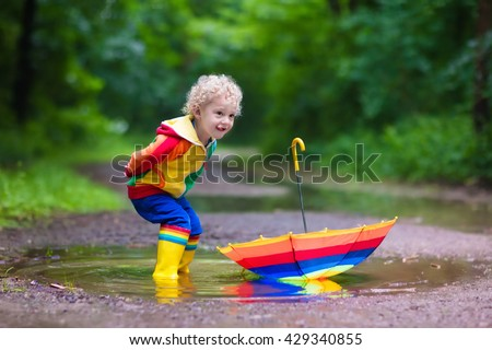 Little boy playing in rainy summer park. Child with colorful rainbow umbrella, waterproof coat and boots jumping in puddle and mud in the rain. Kid walking in autumn shower Outdoor fun by any weather