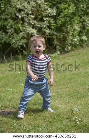 Little boy playing in the garden - stock photo