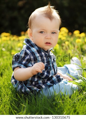 little boy playing in the park in the spring - stock photo