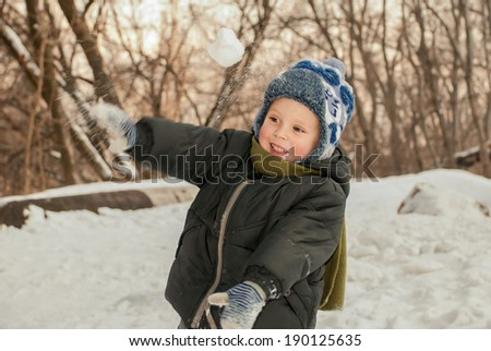 Little boy playing in the snow outdoors in winter. - stock photo
