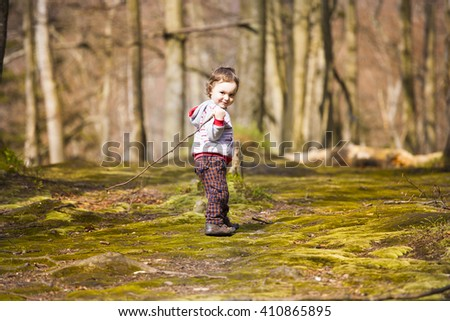 Little boy playing in the woods on a Sunny day.