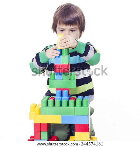 Little boy playing lego on the floor - stock photo