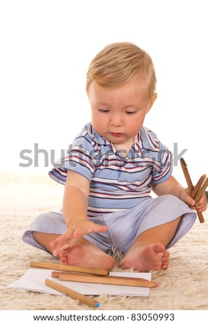 little boy playing on a carpet on white
