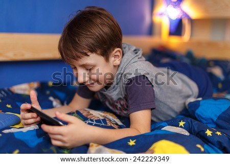 Little boy playing on laptop at home, indoor - stock photo