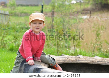 little boy playing on  lawn and  wheel of tractor