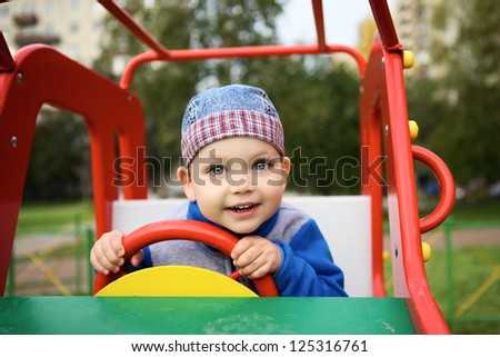 little boy playing on playground in toy car - stock photo