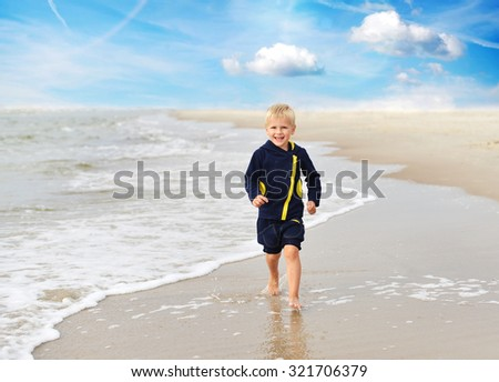 Little boy  playing on  sea beach - stock photo