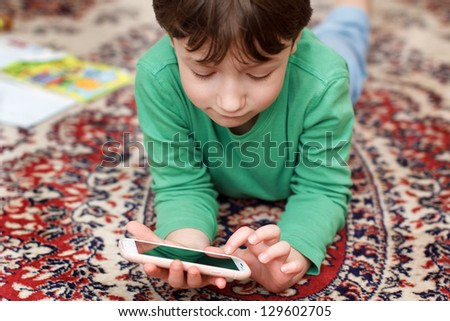 Little boy playing on smartphone - stock photo