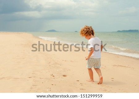 Little boy playing on the beach. - stock photo