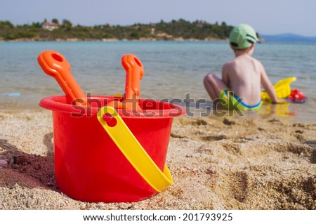Little boy playing on the beach - stock photo