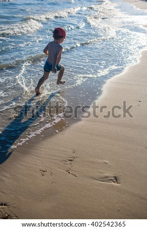 Little boy playing on the beach with sand and waves