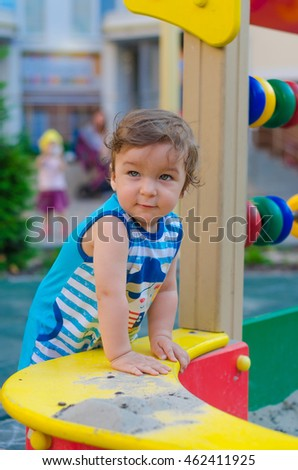 Little boy playing on the playground. Summer, Good weather, colorful toys