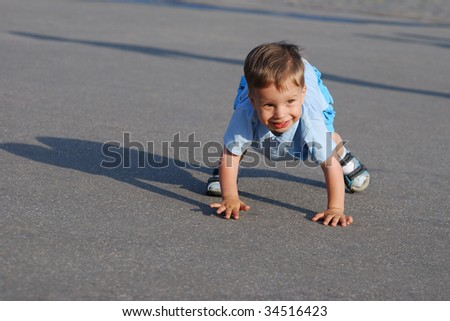 little boy playing on the road - stock photo