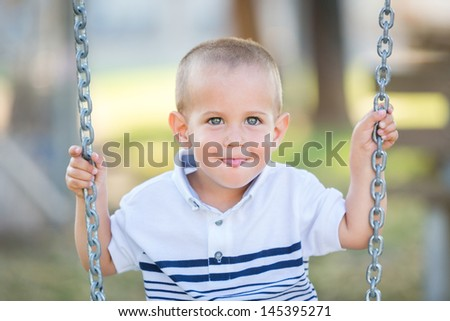 Little Boy Playing on the Swing - stock photo