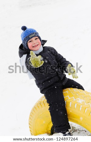 Little boy playing outdoors in snow. Showing thumb up