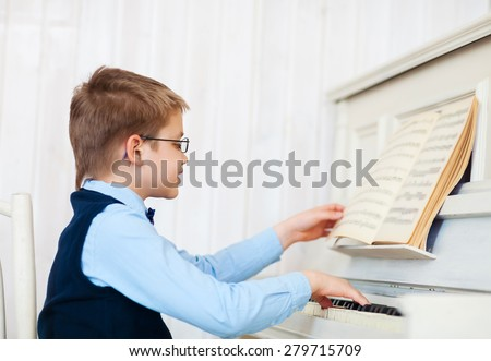 Little boy playing piano at home. Concept of music  - stock photo