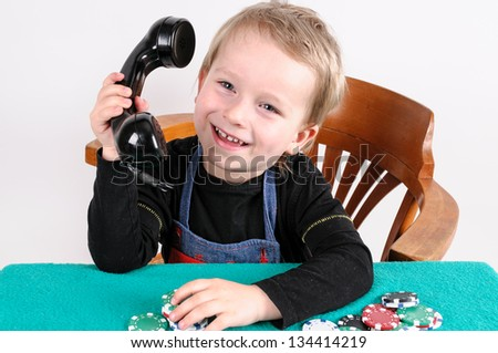little boy playing poker and phones