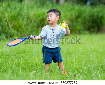 Little boy playing tennis at park - stock photo
