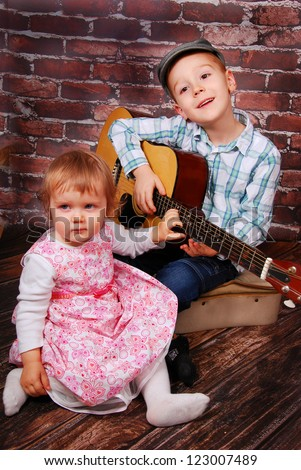 little boy playing the guitar and baby girl sitting in front of him - stock photo