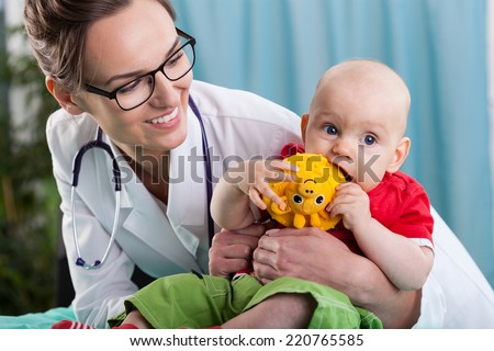 Little boy playing toy and his pediatrician
