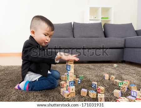 Little boy playing toy block at home - stock photo
