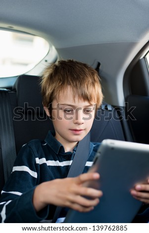 Little boy playing using his tablet inside the car - stock photo