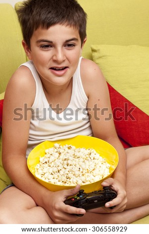 Little boy playing video games and eating popcorn - stock photo