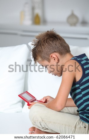 Little boy playing video games on sofa - stock photo