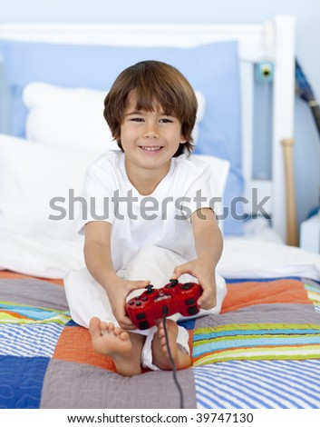 Little boy playing videogames sitting in his bed - stock photo