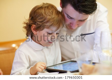 Little boy playing wih his older brother with tablet pc, indoor