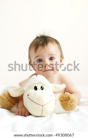 Little boy playing with a lamb