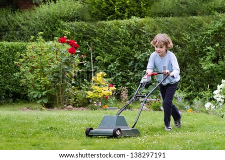 Little boy playing with a lawn mower in the garden - stock photo