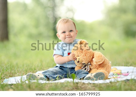 little boy playing with a teddy bear in the grass - stock photo