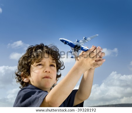 little boy playing with a toy airplane against cloudy blue sky - stock photo